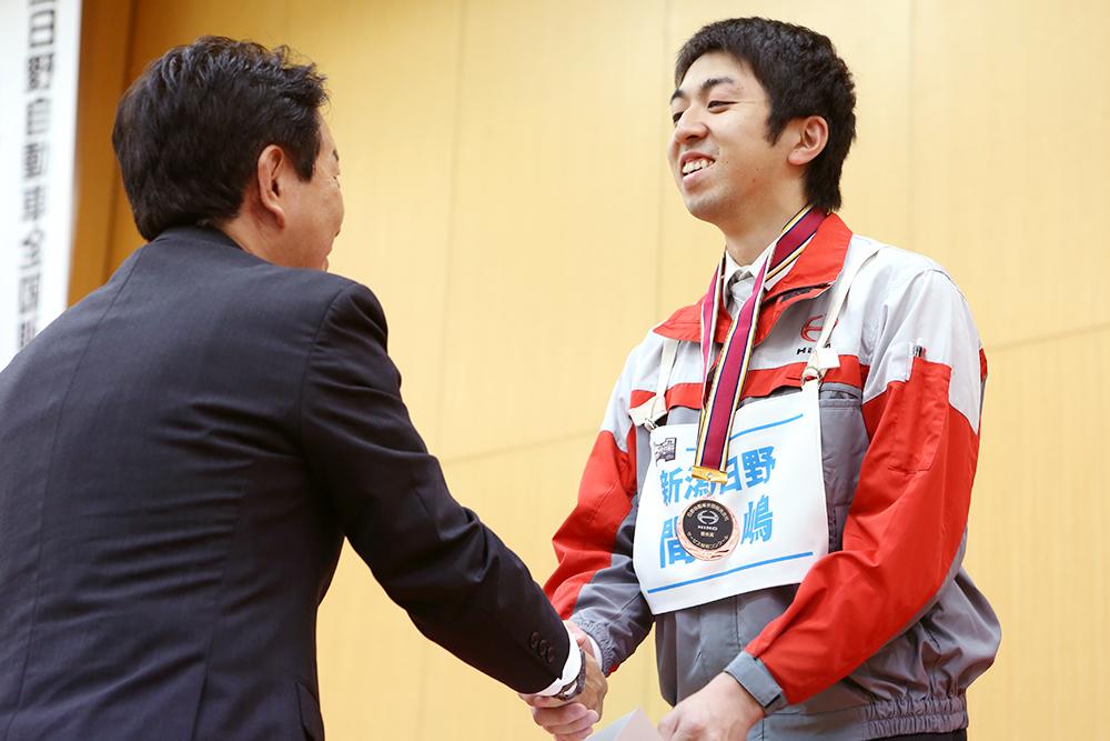 写真:フロントアドバイザー部門で全国3位に入賞した間嶋選手。胸に下げている銅メダルは、努力の結晶を表すかのように輝いています。